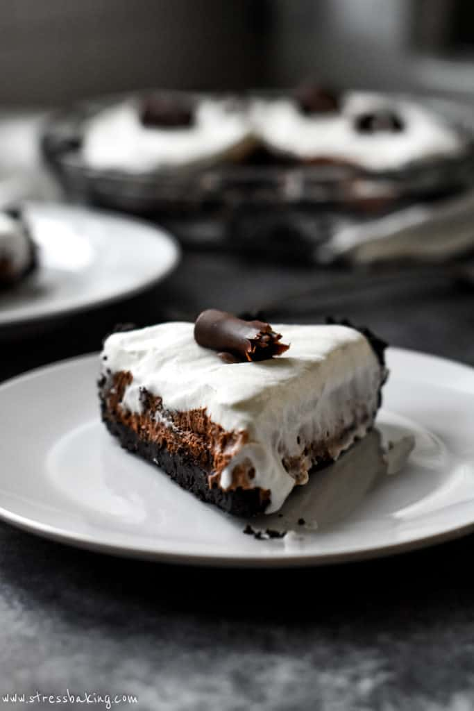 A slice of Bailey's chocolate pie topped with whipped cream and chocolate shavings
