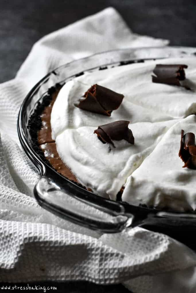 Chocolate pie with a cookie crust topped with whipped cream and chocolate shavings