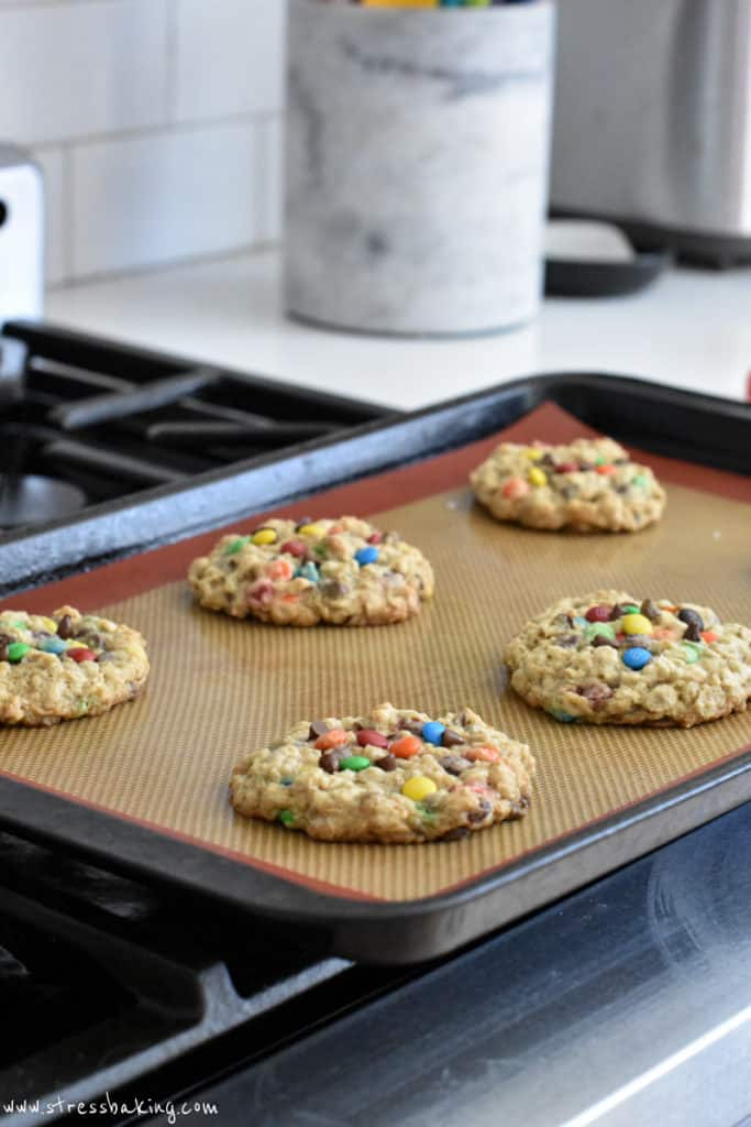Oatmeal M&M cookies cooling on a baking sheet