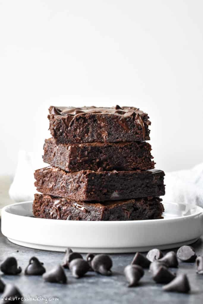 A stack of fudgy brownies with pockets of melted chocolate on a white plate