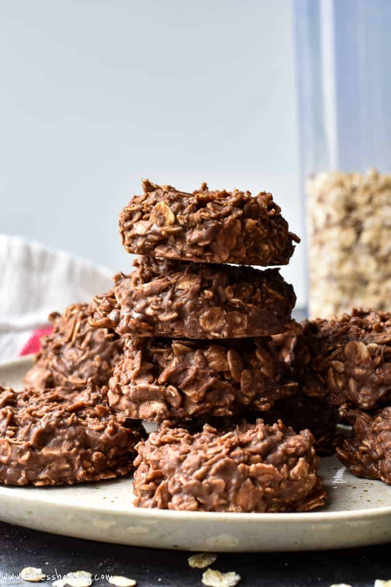Chocolate peanut butter no bake cookies stacked on a cream colored plate