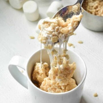 A spoonful of Rice Krispie treat in a white mug being pulled out to show the melty marshmallow