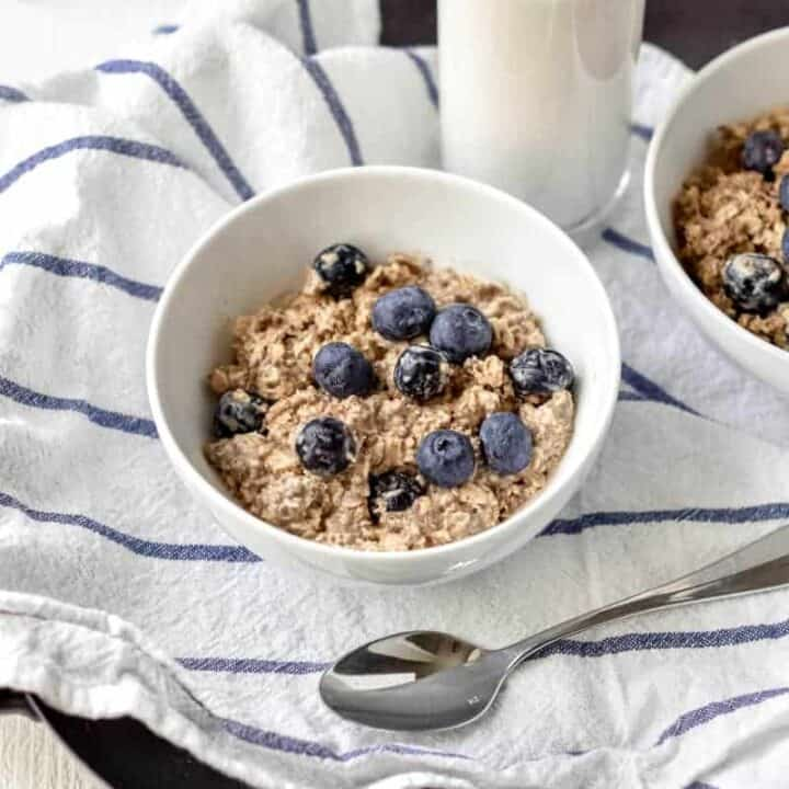 A bowl of brightly colored blueberry overnight oats on a striped dishtowel