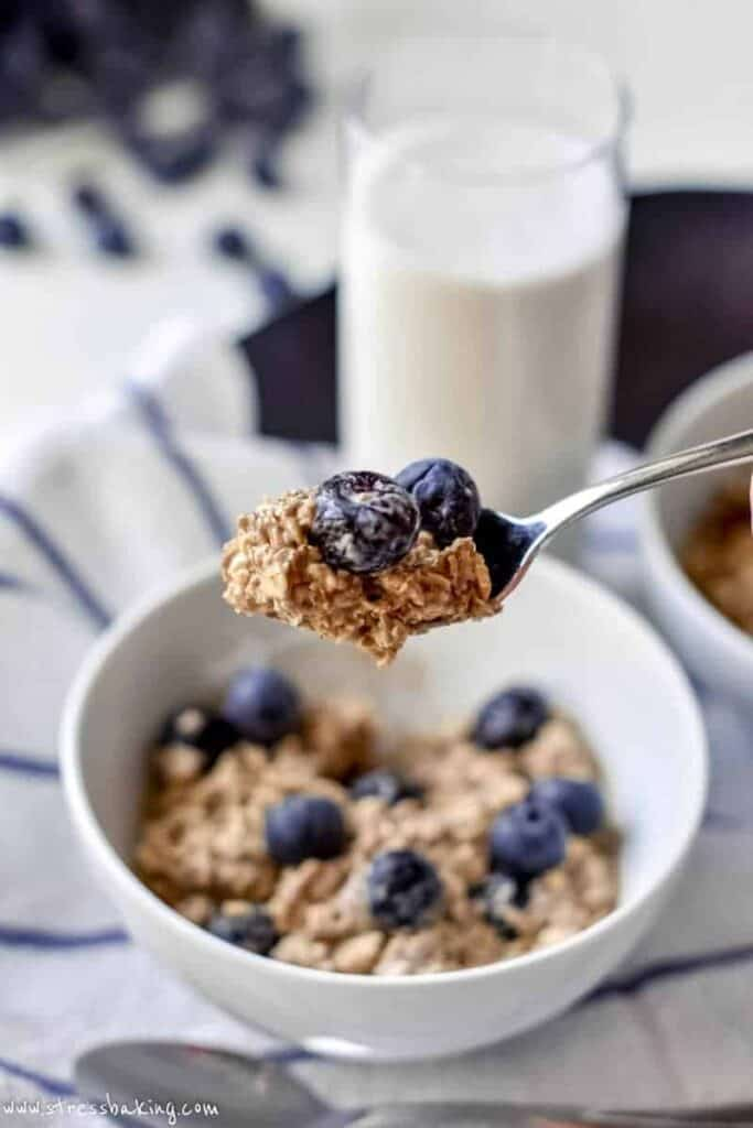 A spoonful of blueberry overnight oats held over a white bowl next to a glass of milk