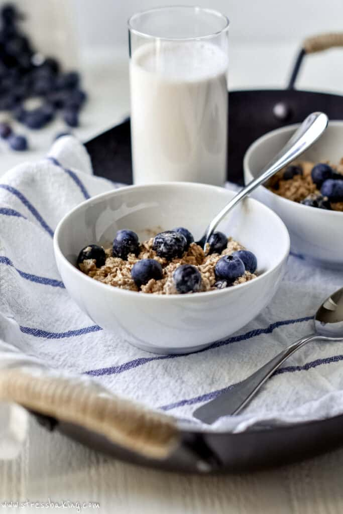 A white bowl full of blueberry overnight oats with a spoon ready to go next to a glass of milk