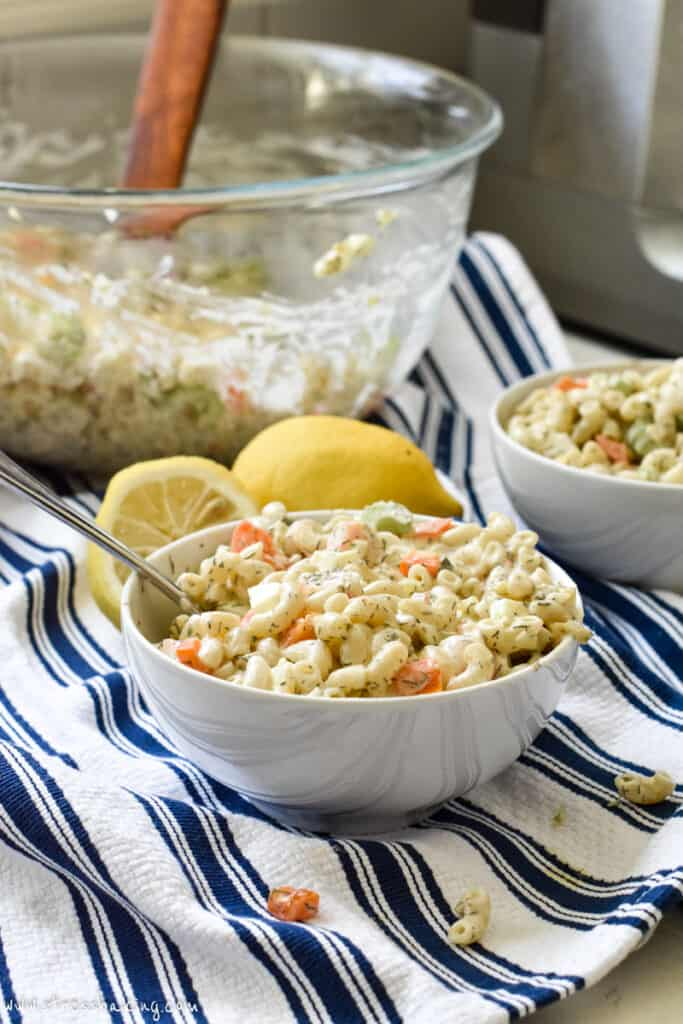 A white bowl of pasta salad on a blue and white dish towel