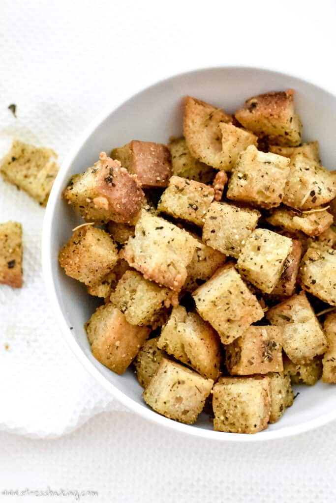 A white bowl full of golden brown croutons