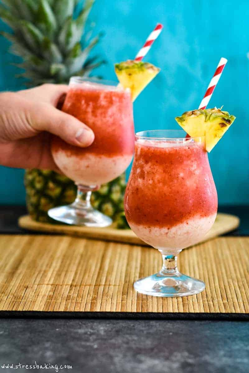 Two vibrant red and cream colored frozen drinks with wedges of pineapple with one being lifted