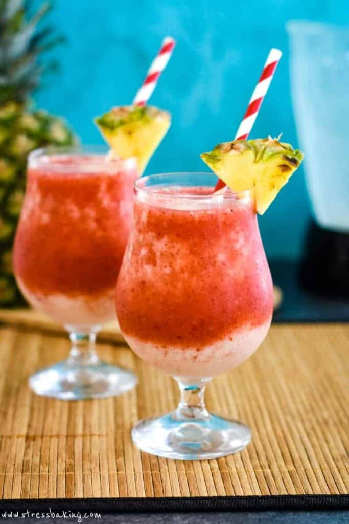 Two vibrant red and cream colored frozen drinks with wedges of pineapple