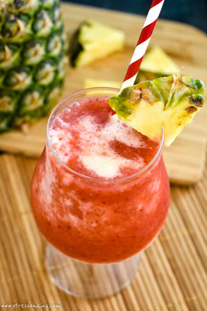 A vibrant red colored frozen cocktail with a wedge of pineapple on a bamboo placemat