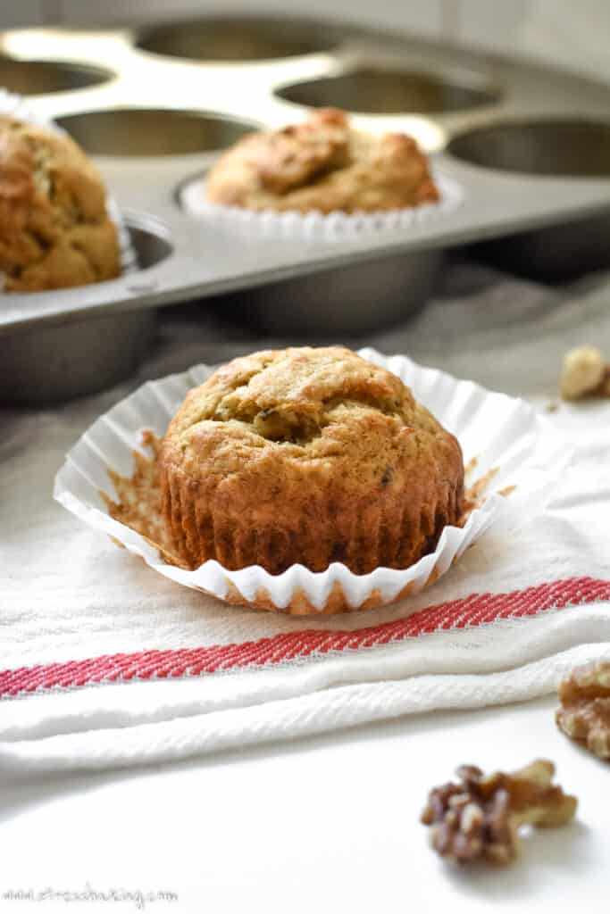 Banana muffin in a white muffin liner on a dishtowel
