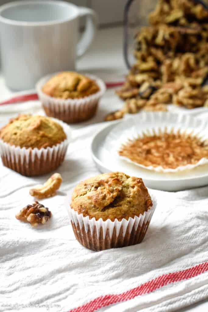 Banana muffins on a white dishtowel with walnuts and a white mug