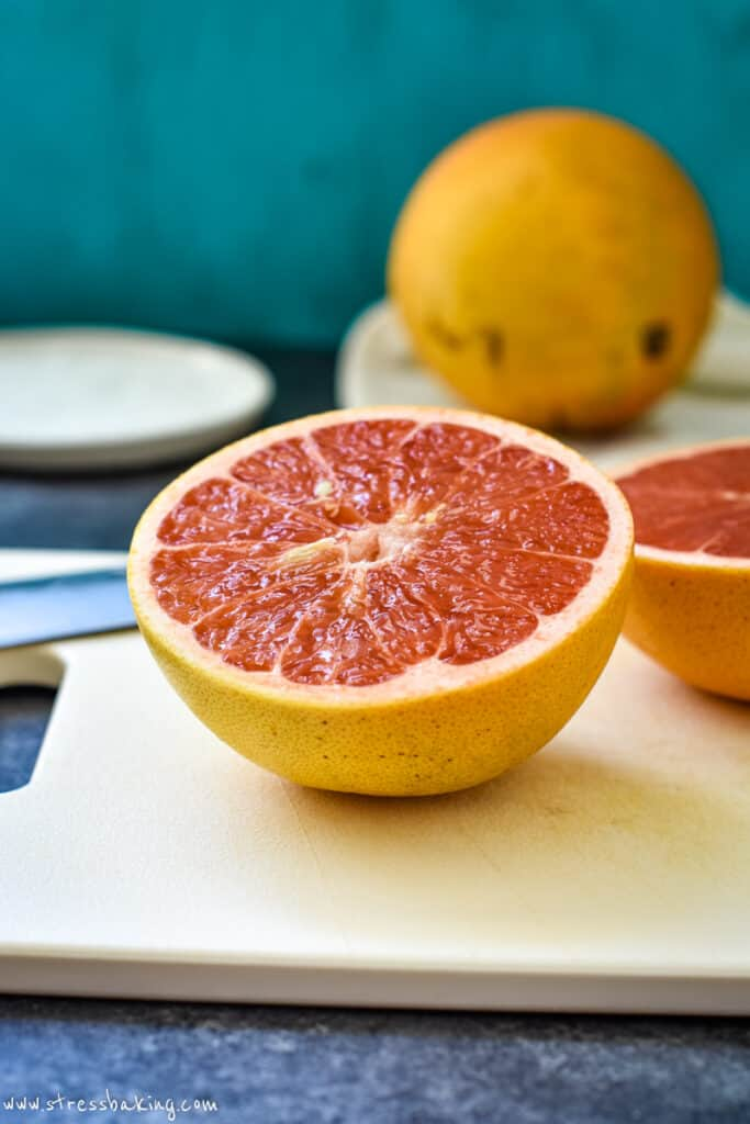 A brightly colored sliced grapefruit half on a white cutting board