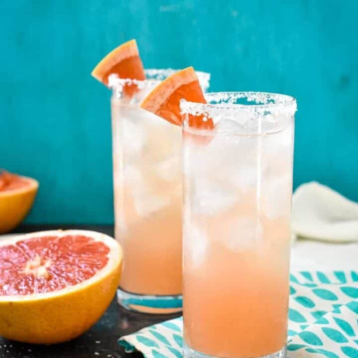 Colorful Salty Dogs in a highball glass in front of a teal background