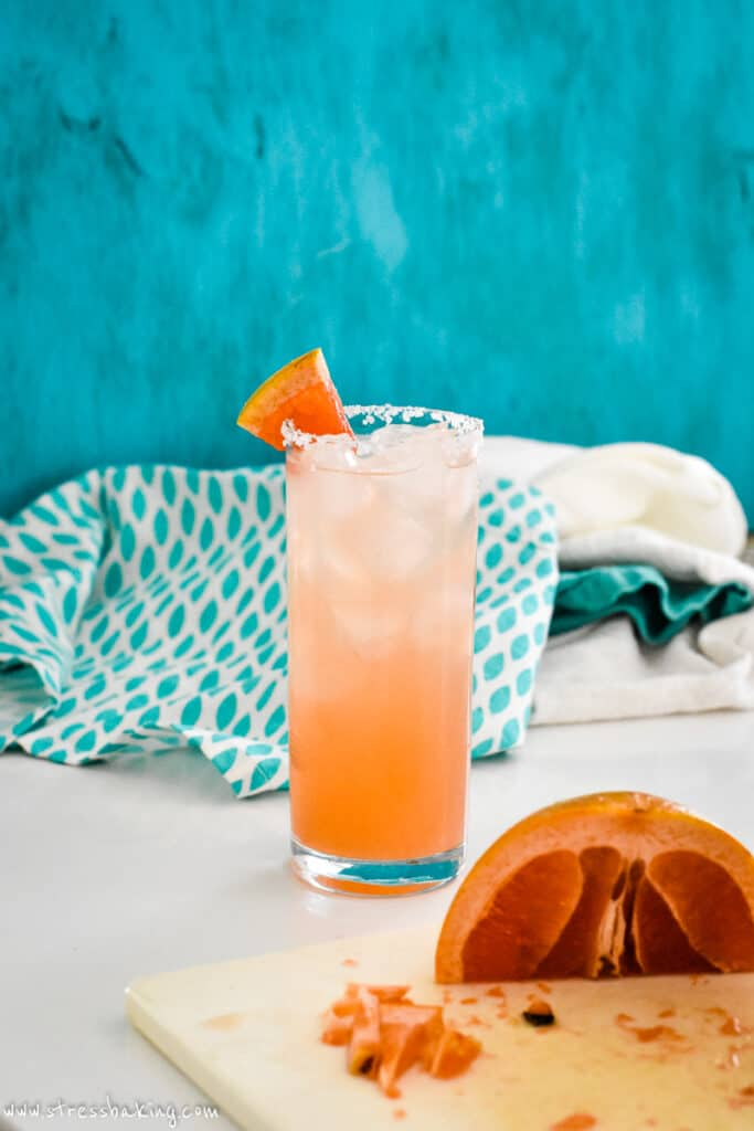 A colorful Salty Dog in a highball glass in front of a teal background
