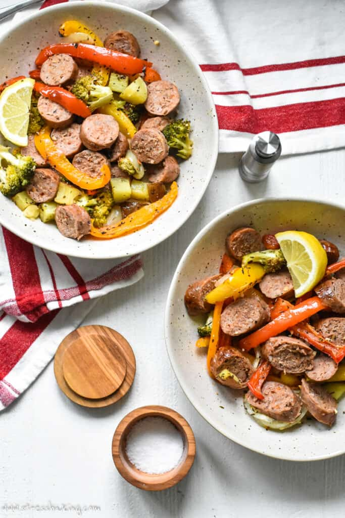 Two bowls of sliced sausage and colorful roasted vegetables