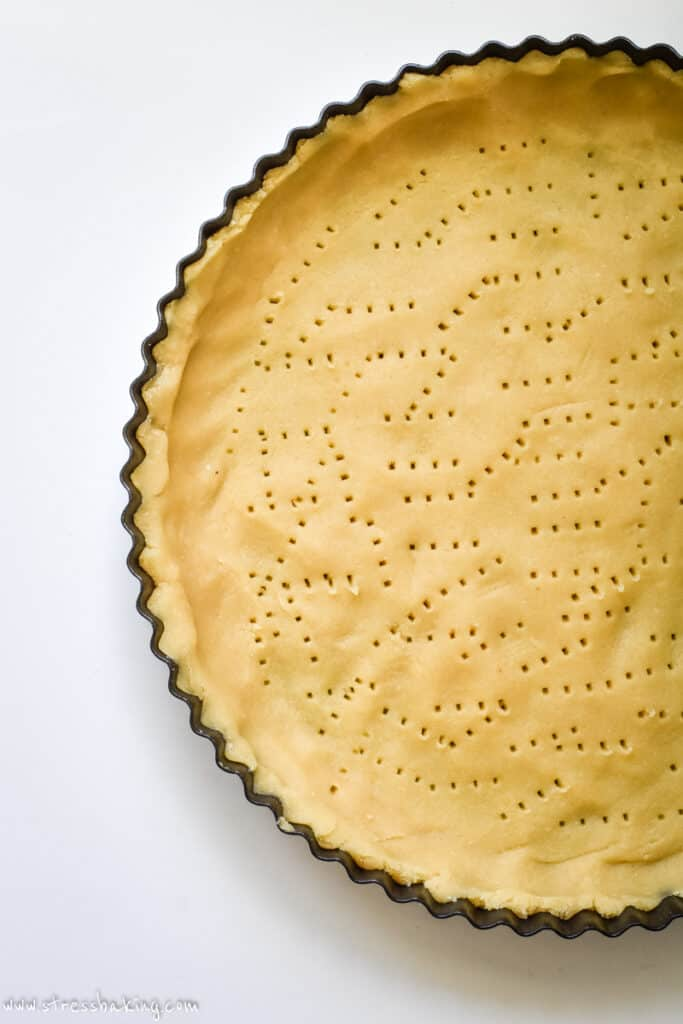 A tart crust with holes poked in the bottom