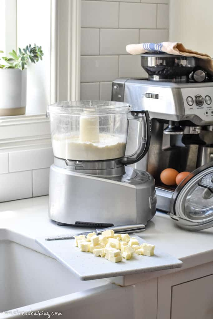 A food processor on a counter with cubed butter and an espresso machine