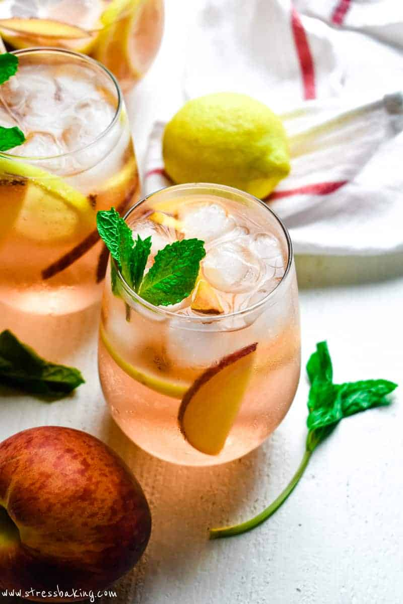 A glass of rose colored sangria and fruit garnished with fresh mint