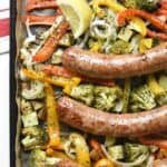 Overshot photo of browned sausages on top of a sheet pan of seasoned roasted veggies