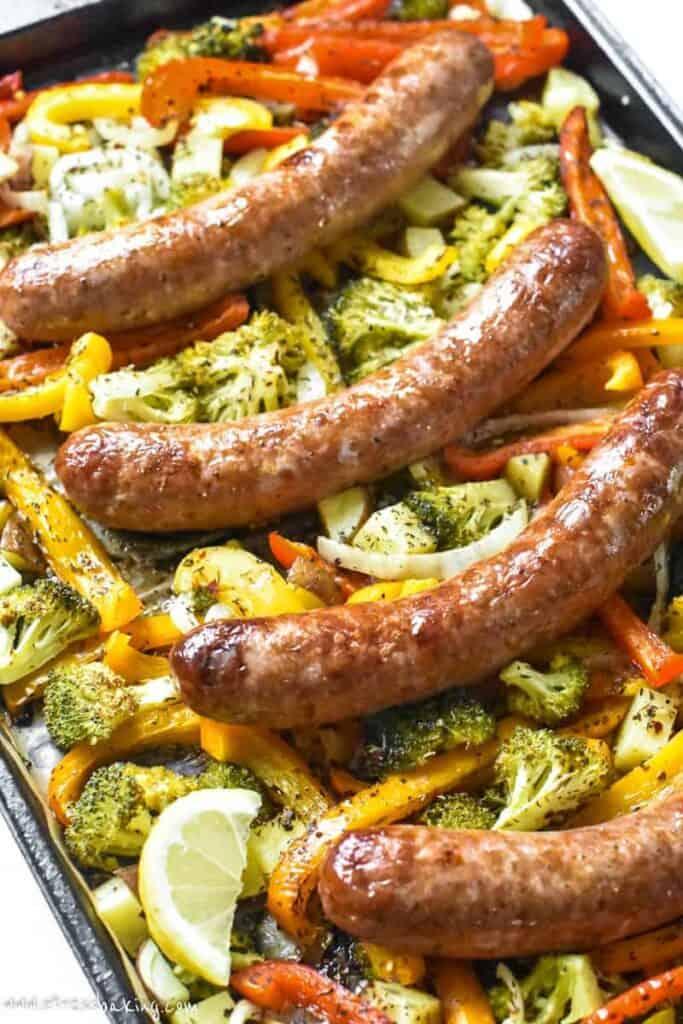 Overshot photo of browned sausages on top of a sheet pan of seasoned roasted veggies