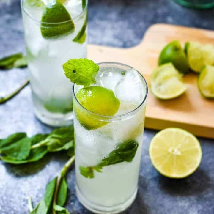 Two mojitos with bright green mint and limes