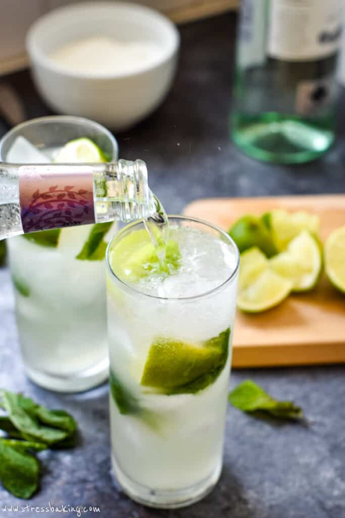 Tonic water being poured into a glass of mojito