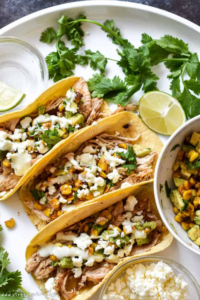 Three mexican street corn tacos on a white platter with limes and cilantro