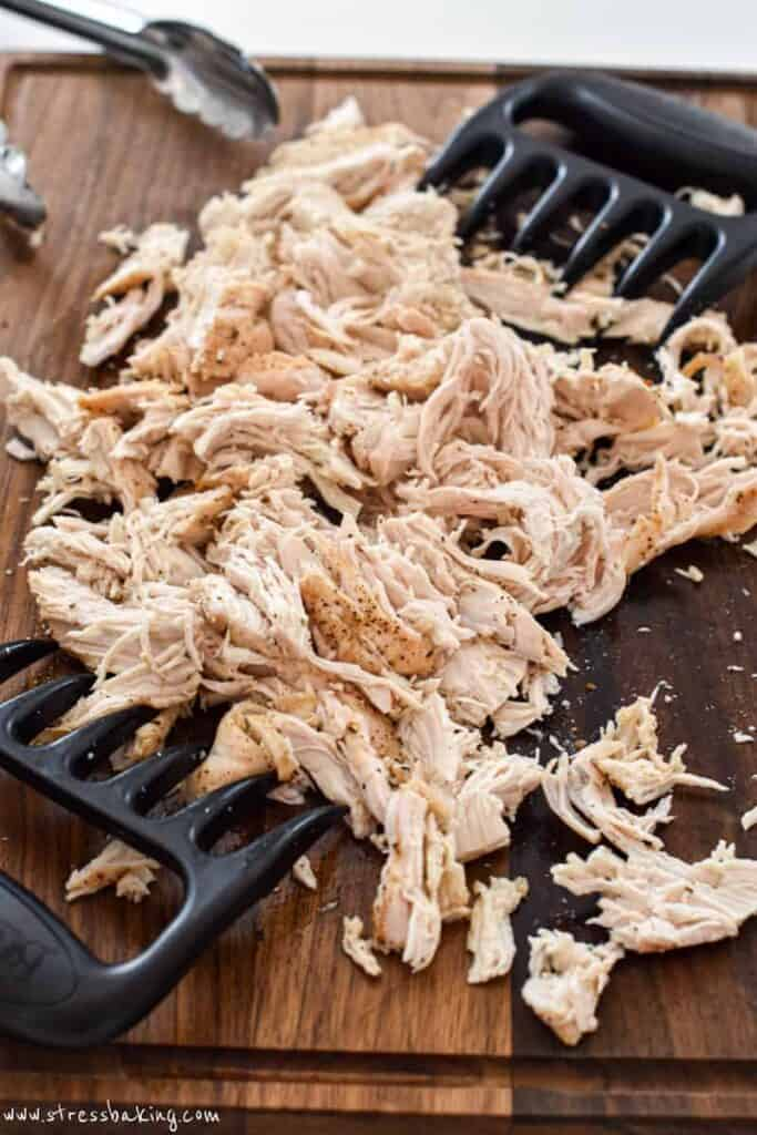Pile of shredded chicken on a cutting board
