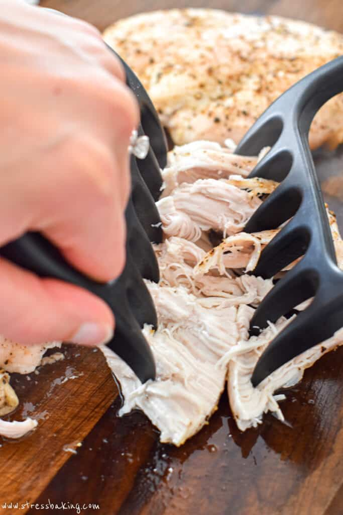 Shredding a chicken breast with two meat claws