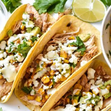 Three mexican street corn tacos on a white platter