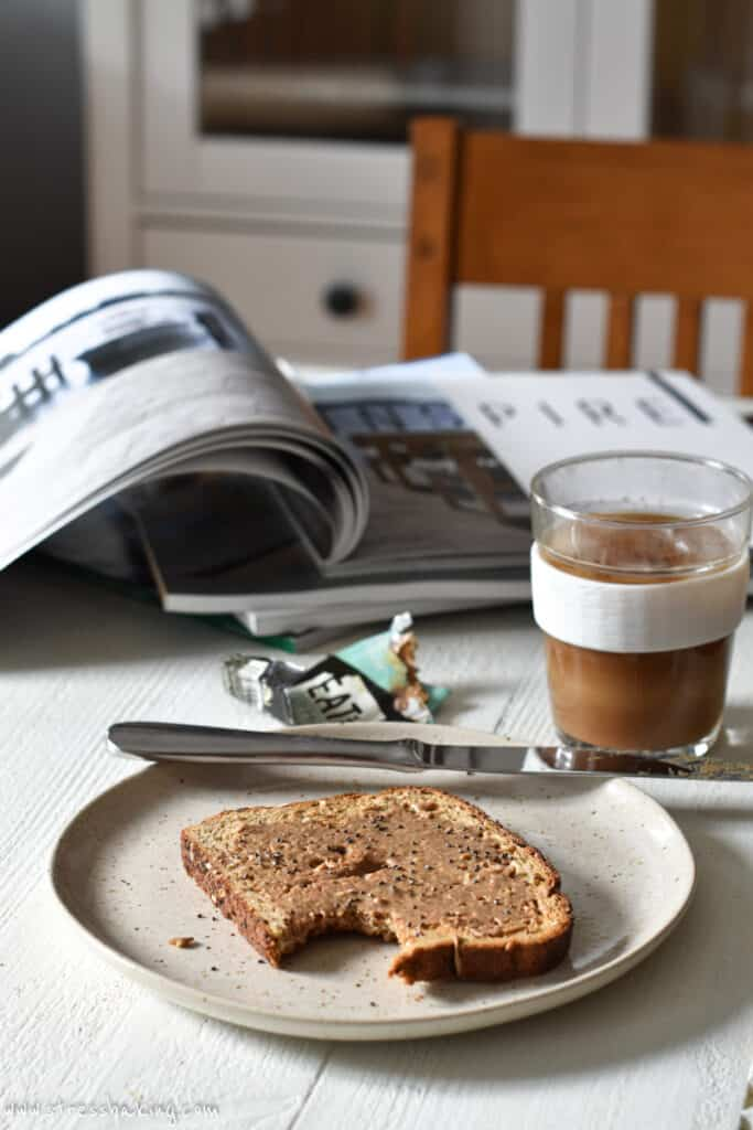 A piece of toast covered in nut butter next to magazines