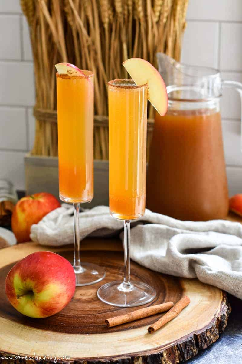 Two apple cider champagne cocktails in a fall setting