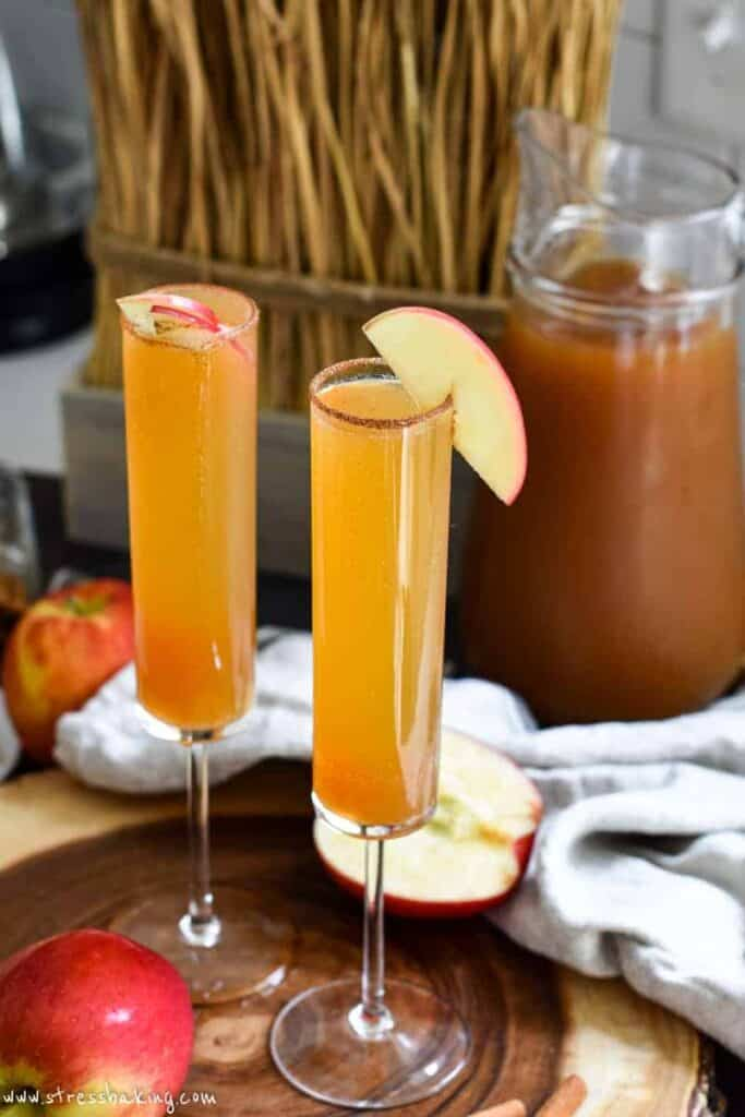 Apple cider champagne cocktails garnished with thin apple slices