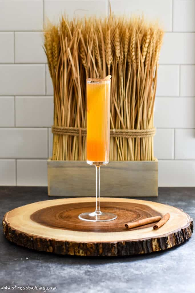 A single champagne flute on a wooden platter