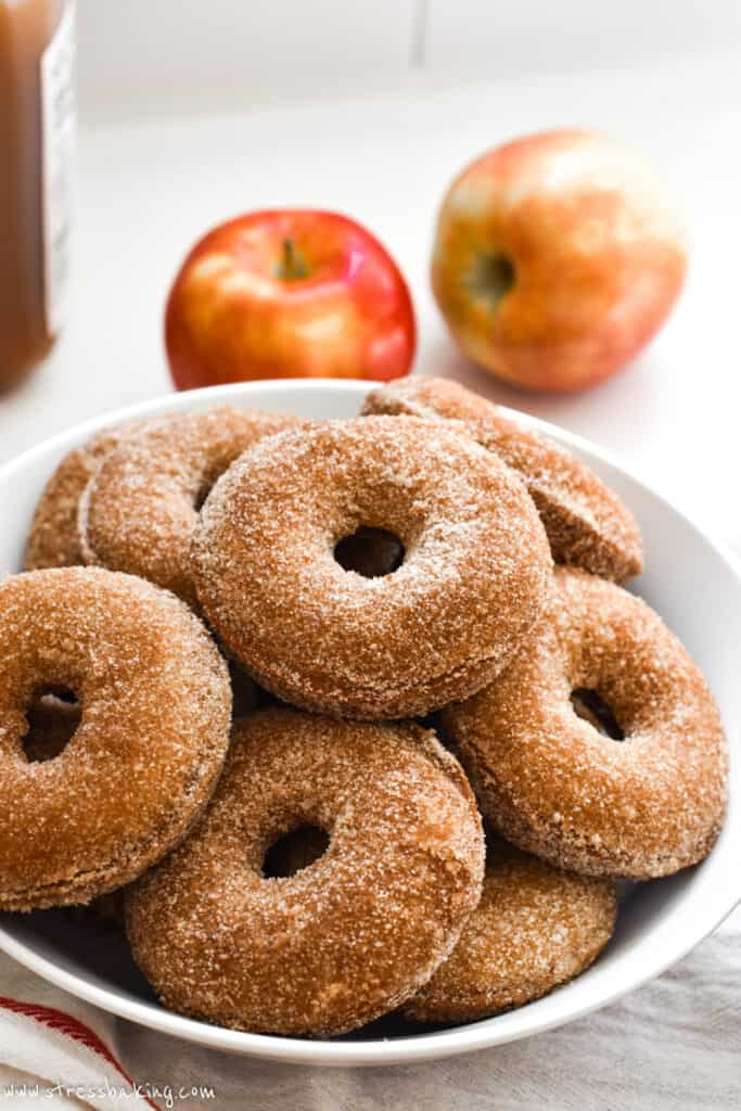 A pile of apple cider donuts in a white bowl