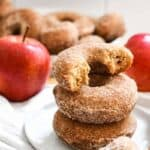 A stack of apple cider donuts on a white plate with red apples
