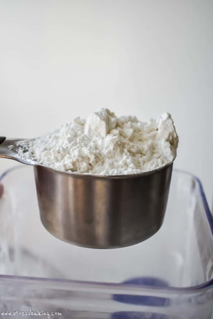 A measuring cup full of a mound of all purpose flour