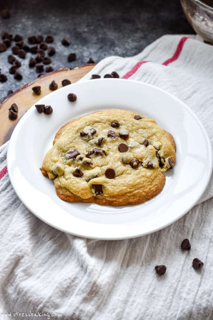 A big golden brown chocolate chip cookie on a white plate