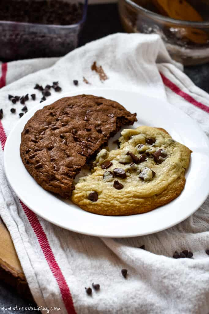 Half a chocolate chip cookie and half a double chocolate chip cookie on a white plate