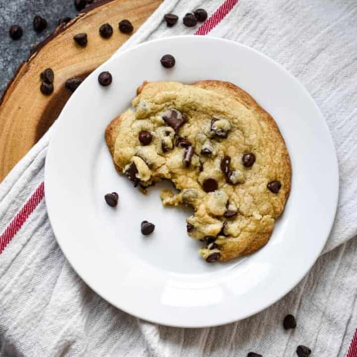 Giant crinkly chocolate chip cookie with a chunk missing on a white plate