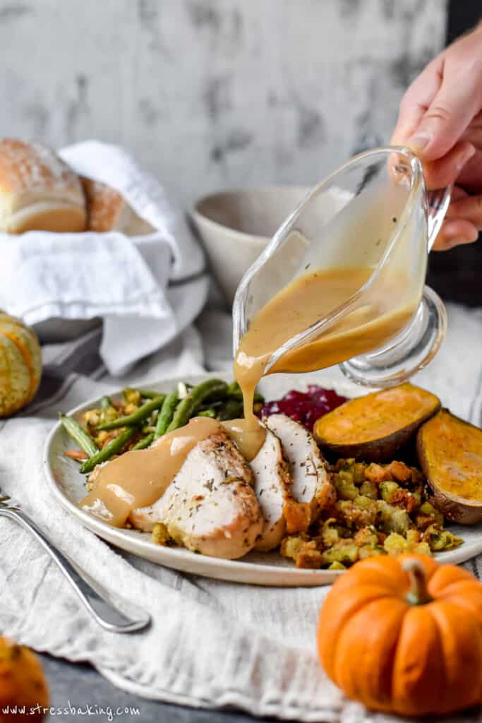 Gravy being poured onto thick slices of turkey breast surrounded by Thanksgiving foods