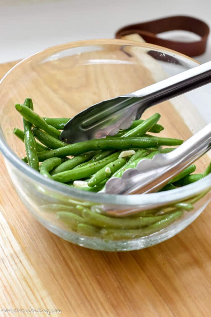 A clear bowl of green beans with a pair of tongs