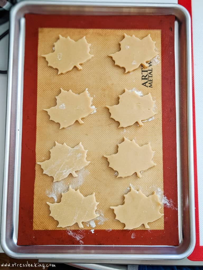 Maple leaf cutout cookies on a baking sheet