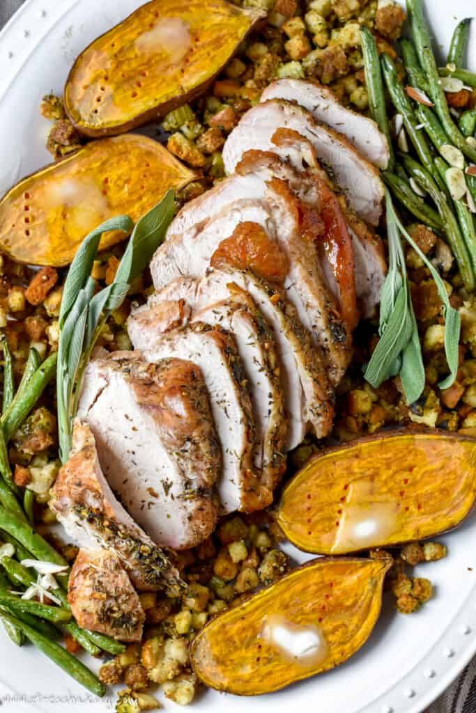 Thick slices of seasoned turkey breast nestled on top of platter of stuffing, green beans and sweet potatoes
