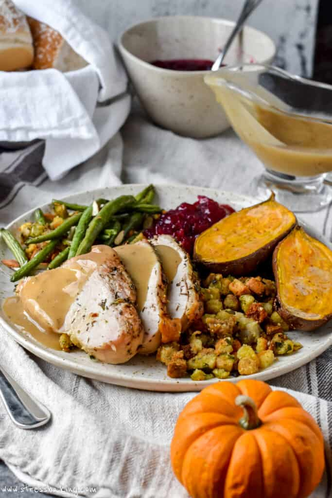 A plate full of Thanksgiving dinner foods on a linen cloth