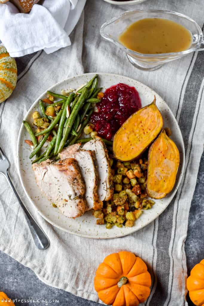 Overhead shot of a plate full of Thanksgiving dinner on a linen cloth