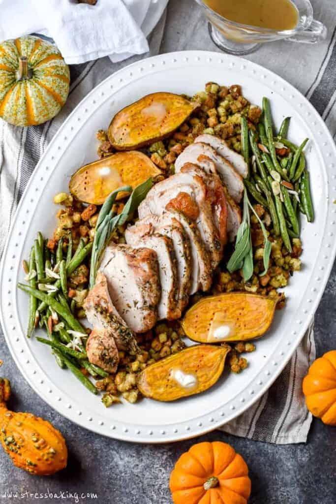 White platter full of turkey, stuffing, green beans and sweet potatoes