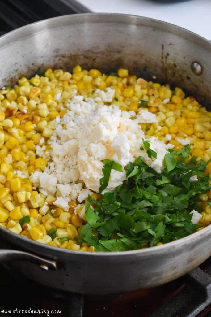 Mexican corn dip in a pan with cheese and cilantro