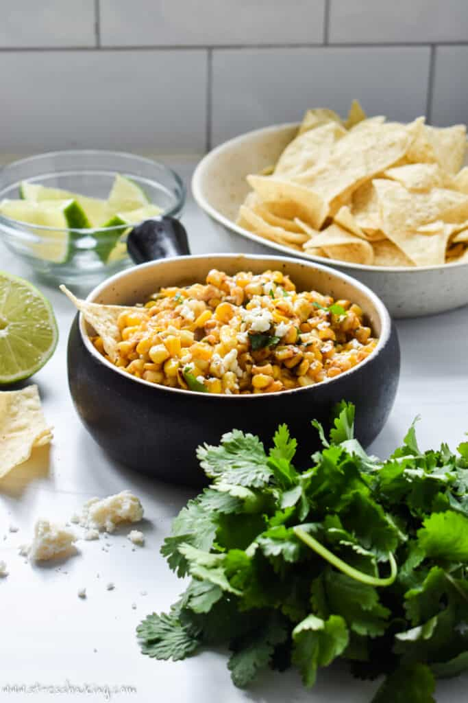A crock of Mexican corn dip on a counter with bowl of chips and other garnishes